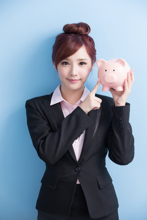 1: business woman take pink piggy bank and smile to you with isolated on blue background Stock Photo
