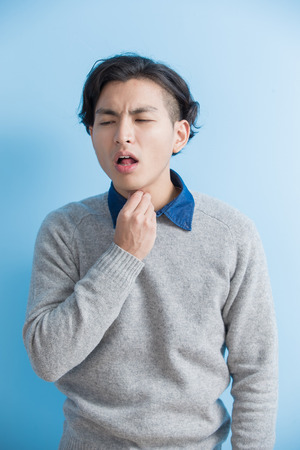 man student feel sore throat with blue background, asian