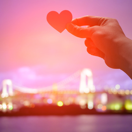 travel woman: silhouette of romantic lovers hand hold love heart paper in Odaiba with sunset