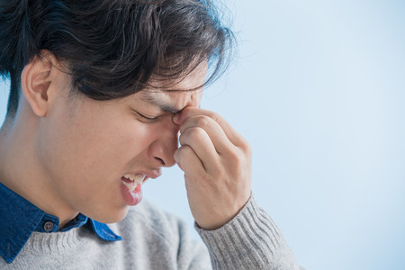 Estudiante del hombre se siente molestias en los ojos con el fondo azul aislado, asiático Foto de archivo