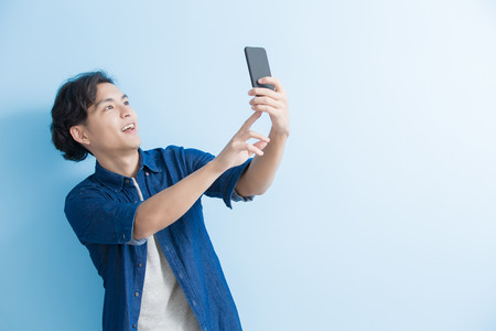 asian guy: man student smile and selfie isolated on blue background,asian