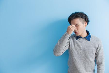 man feel headache with blue background, asian Stock Photo