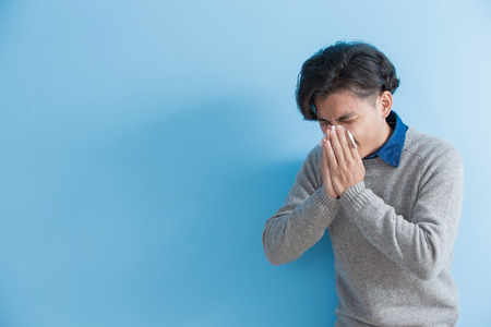 man is sick and sneezing with blue background, asian Stock Photo