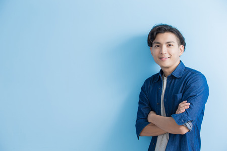 man student smile to you isolated on blue background,asian