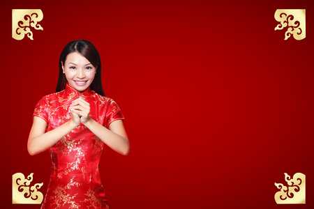 gesturing: Smile Chinese woman dress traditional cheongsam and introduce on red background. asian beauty Stock Photo