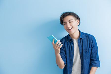 Estudiante del hombre sonrisa y el uso del teléfono aislado en el fondo azul, asiático