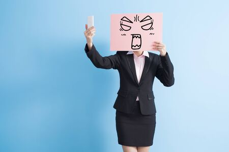 billboard background: business woman take angry billboard and selfie, isolated blue background