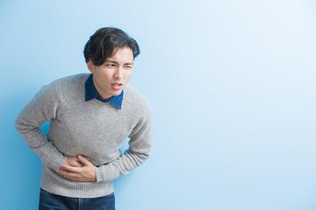 man voelt maagpijn met geïsoleerde blauwe achtergrond, aziatisch Stockfoto