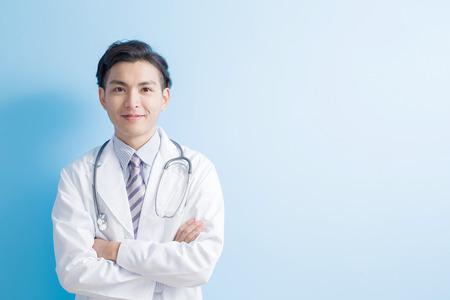 分離の青い背景を持つアジアの男性医師あなたに笑顔します。 写真素材