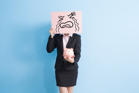 businesswoman take cry billboard and show piggy bank to you isolated with blue background 免版税图像