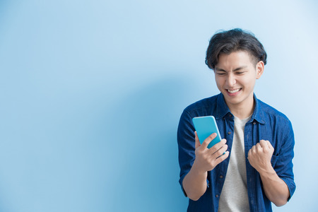 man student smile and use phone isolated on blue background,asian Stock Photo