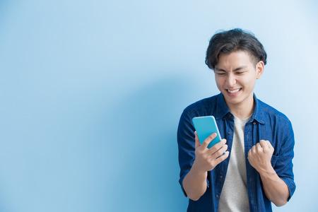 Mann Student Lächeln und Benutzen Sie das Telefon auf blauem Hintergrund, asiatisch Standard-Bild - 66990934