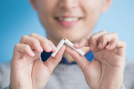 男は、青色の背景に喫煙をやめるアジア