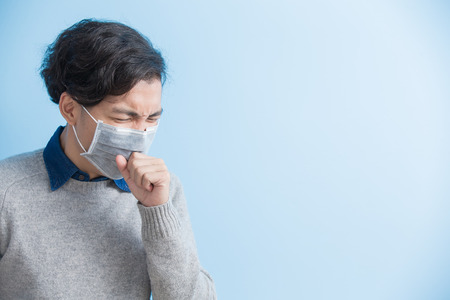 man is coughing isolated on blue background, asian Stockfoto