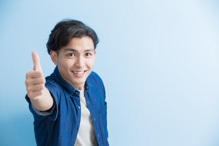 男は笑顔と青い背景に分離するまで親指をアジアに表示 写真素材
