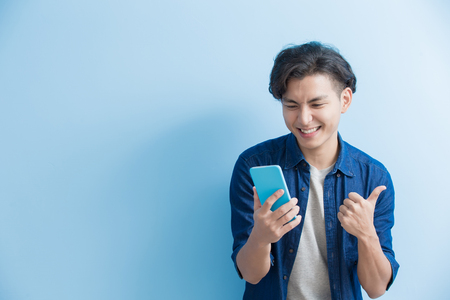 man student smile and use phone isolated on blue background,asian Banco de Imagens