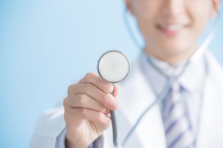 mannelijke arts toont stethoscoop aan u, Aziatische