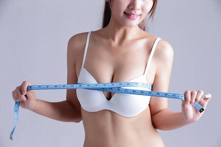 junge nackte mädchen: junge Frau, die ihre Brust-Messung isoliert auf grauem Hintergrund, asiatische Schönheit