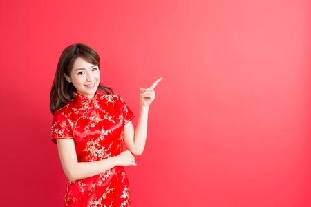美容女性チャイナ ドレスを着用し、中国の新年に何かを示さなければ