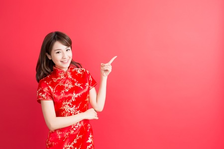 beauty woman wear cheongsam and show something to you in chinese new year Stock Photo