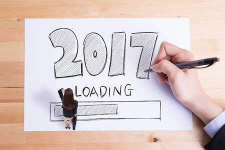 see: Business people writing 2017 new year loading text on the paper and woman feel confuse Stock Photo