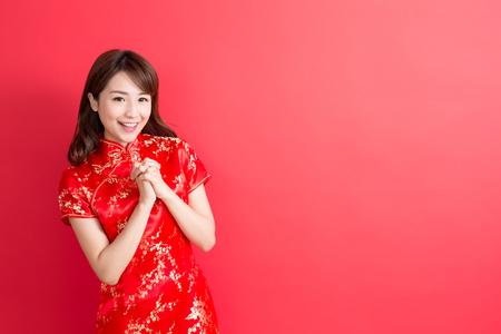 美容女性のチャイナ ドレスを着用し、中国の旧正月であなたに微笑む 写真素材