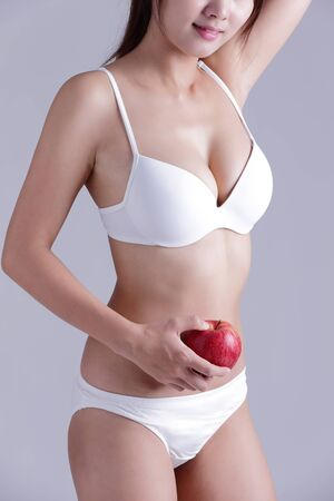 waistline: Fit woman hold apple isolated on the gray background, asian
