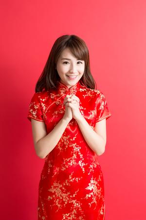 Mujer de la belleza del desgaste del cheongsam y la sonrisa a usted en el año nuevo chino Foto de archivo - 68326642