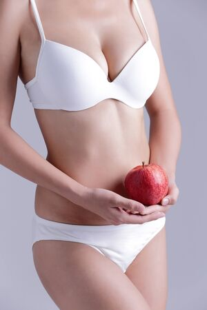 Fit woman hold apple isolated on the gray background, asian