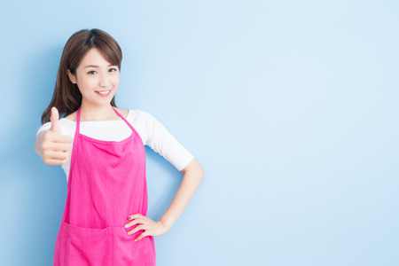 beauty housewife thumb up and smile to you isolated on blue background, asian