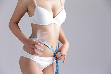 forme et sante: l'eau et le corps de la femme Santé - femme, mesurer la forme de la belle taille pour un mode de vie sain concept de fond gris, la beauté asiatique