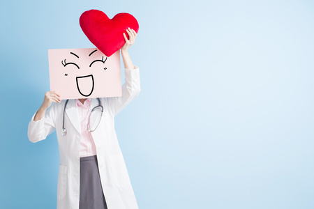 woman doctor take smile billboard and heart isolated on blue backgorund, asian