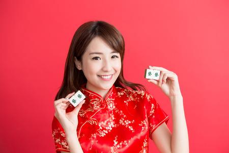 mahjong: beauty woman wear cheongsam and show mahjong to you in chinese new year