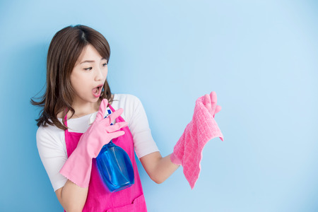 girl home: beauty housewife take rag and detergent feel surprise isolated on blue background, asian