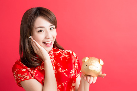 beauty woman wear cheongsam and show gold piggy bank to you in chinese new year Stock Photo