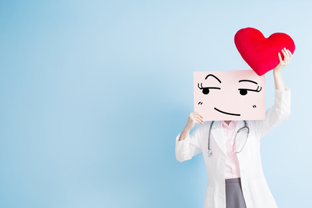 woman doctor take look somewhere billboard and heart isolated on blue backgorund, asian Stock Photo