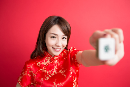 asia women: beauty woman wear cheongsam and show mahjong to you in chinese new year