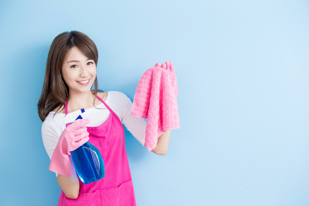 beauty housewife take rag and detergent isolated on blue background, asian 版權商用圖片