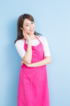 beauty housewife look and smile to you isolated on blue background, asian