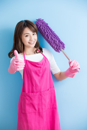 beauty housewife take feather duster and thumb up isolated on blue background, asian