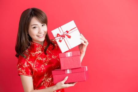 아름다움 여자 치파오를 착용 하 고 중국 새 해에 당신에 게 선물 상자를 표시 스톡 콘텐츠
