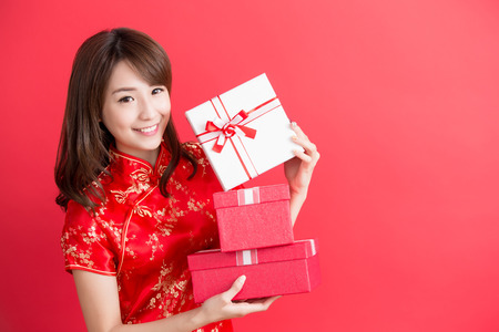beauty woman wear cheongsam and show gift box to you in chinese new year 版權商用圖片