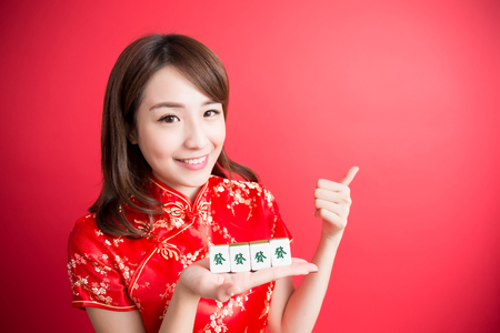 chinese lady: beauty woman thumb up and show mahjong to you in chinese new year - Rich and wealthy text on girl hand in Chinese words