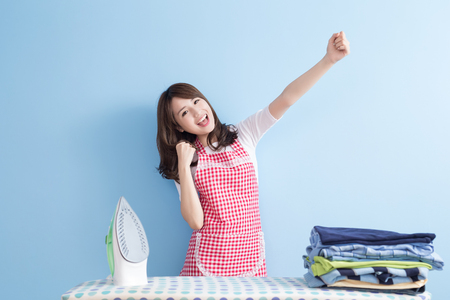work at home: beauty  housewife with ironing and shirt isolated on blue background