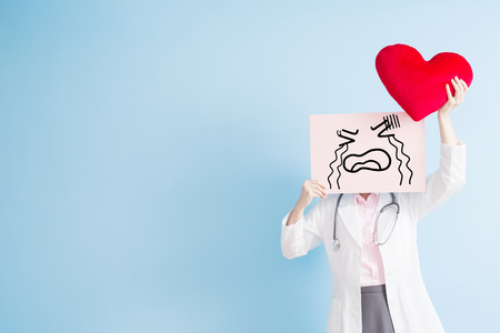 sad heart: woman doctor take cry billboard and heart isolated on blue backgorund, asian