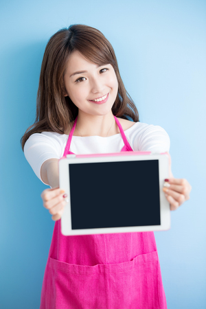lady on phone: beauty housewife take tablet and smile isolated on blue background, asian Stock Photo