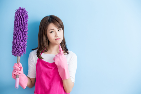 beauty housewife take feather duster and unhappy isolated on blue background, asian