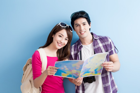 young couple take map and smile happily isolated on blue background Stock Photo