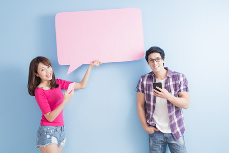 young couple take phone and speech bubble isolated on blue background Stock Photo