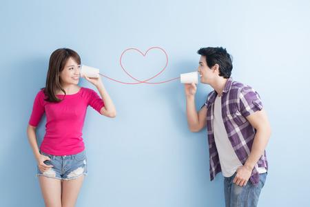 junges Paar mit Dosentelefon auf blauem Hintergrund isoliert